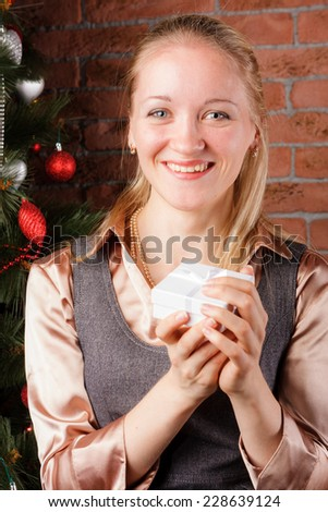 Smiling beautiful woman holding small gift box under the Christmas tree - stock photo