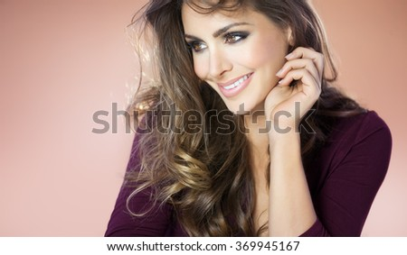 Smiling beautiful woman in purple shirt. Fashion and beauty concept in studio.