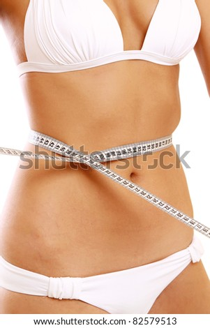 smiling beautiful woman in swimsuit looking at measure on white background