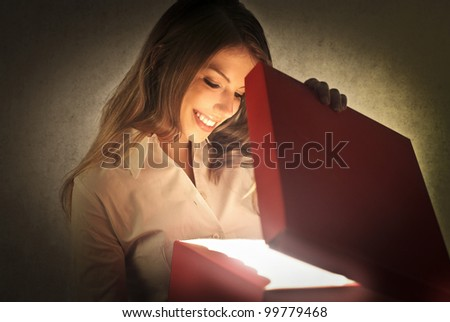 Smiling beautiful woman opening a present - stock photo