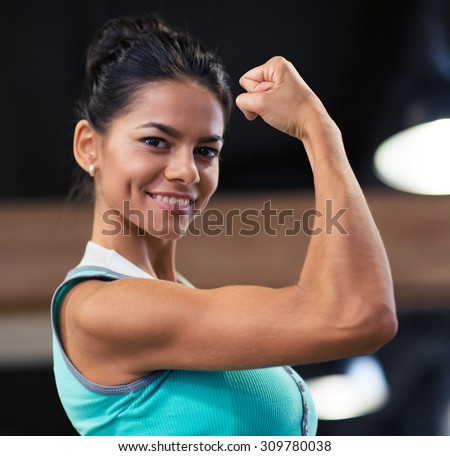 Smiling beautiful woman showing her biceps in gym - stock photo