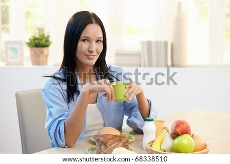 Smiling beautiful woman sitting at breakfast table, holding cup, looking at camera.