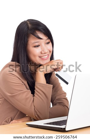 smiling beautiful Woman sitting at the desk, shopping with laptop and credit card - stock photo