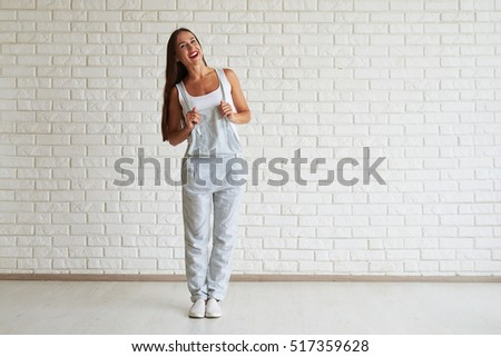 Smiling beautiful woman standing and clings overalls with both hands, white brick wall on background