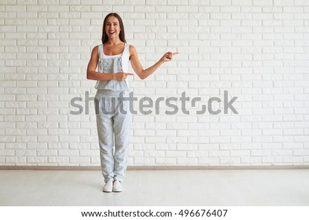 Smiling beautiful woman standing and points with both hands to the side, white brick wall on background