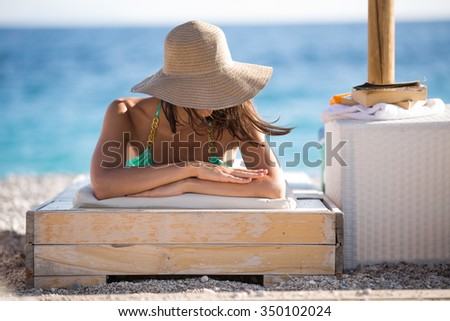 Smiling beautiful woman sunbathing in a bikini on a beach at tropical travel resort, enjoying summer holidays. Young woman lying on sun lounger near the sea. Happy serene woman having SPF protection - stock photo