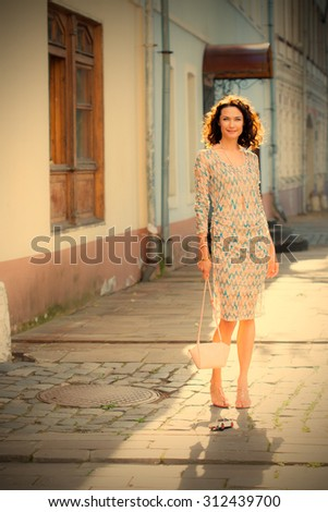 smiling beautiful woman with a small handbag on the ancient street. instagram image filter retro style - stock photo