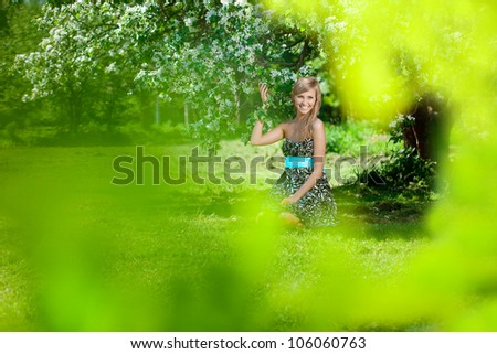 Smiling beautiful woman with flowering tree