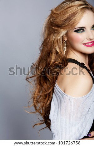 smiling beautiful woman with long curly blond hair wearing bright pink lipstick and smoky eyeshadow on studio background. - stock photo