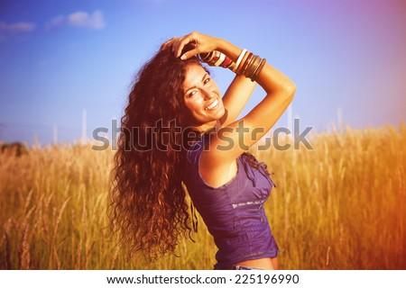 smiling beautiful woman with long curly hair enjoy in sun and nature  in grass field - stock photo