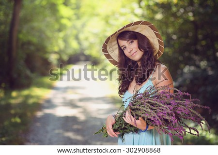 Smiling beautiful woman with wild flowers . Country portrait