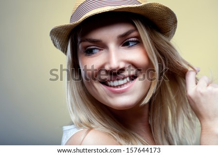 Smiling beautiful young blond woman in a trendy hat, close up portrait
