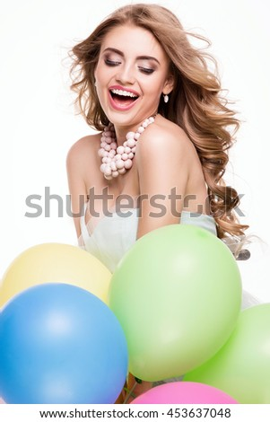 Smiling beautiful young blonde woman dancing with colorful balloons. Studio shot. Happiness.