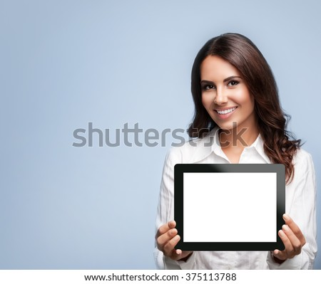 Smiling beautiful young brunette businesswoman showing blank no-name tablet pc monitor, over grey background, with copyspace area for slogan or text message - stock photo