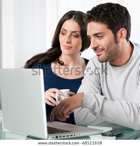 Smiling beautiful young couple surfing the net with laptop at home