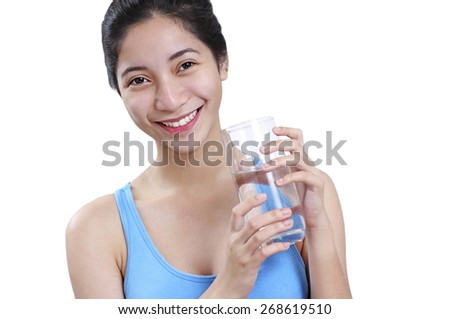 Smiling beautiful young lady holding a glass of drinking water. Isolated in white background. - stock photo