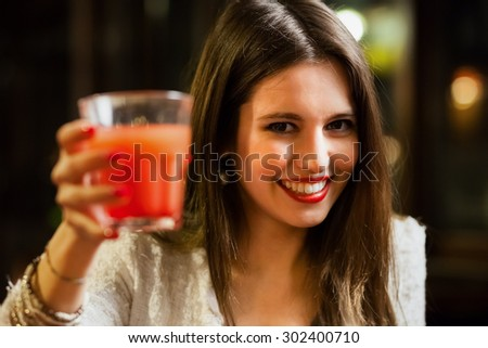Smiling beautiful young woman holding a cocktail glass - stock photo