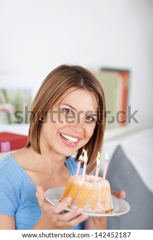 Smiling beautiful young woman holding a small round birthday cake in her hands with burning candles