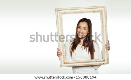 Smiling beautiful young woman holding an old white painted wooden picture frame so that it frames her face over a white studio background with copyspace - stock photo