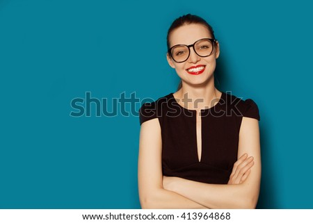 Smiling beautiful young woman in glasses. Business studio portrait on blue background  - stock photo