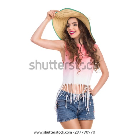 Smiling beautiful young woman in jeans short, pink top and straw hat standing and looking away. Three quarter length studio shot isolated on white. - stock photo