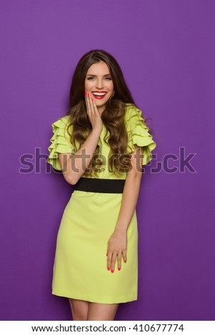 Smiling beautiful young woman in lime green dress posing with hand on chin and looking at camera. Three quarter length studio shot on purple background. - stock photo