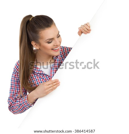Smiling beautiful young woman in lumberjack shirt peeking behind white banner and reading. Head and shoulders studio shot isolated on white.