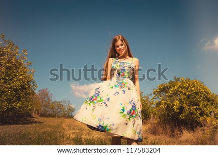 smiling beautiful young woman in silky dress walk in meadow sunny day - stock photo