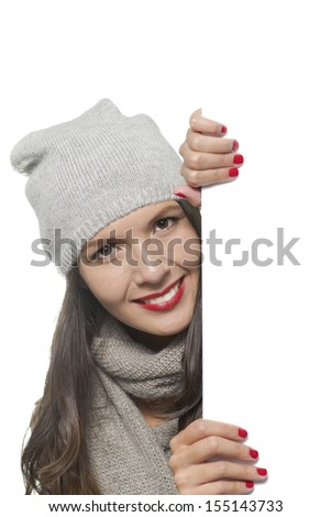 Smiling beautiful young woman in stylish winter fashion holding a blank white sign with copy space for your text or advertisement