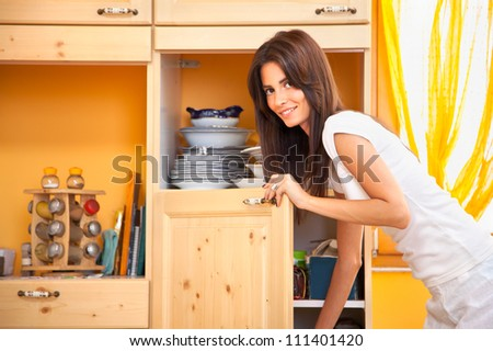 Smiling beautiful young woman in the kitchen - stock photo