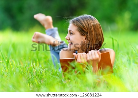 Smiling beautiful young woman lying on grass and reading book, against background of summer green park.