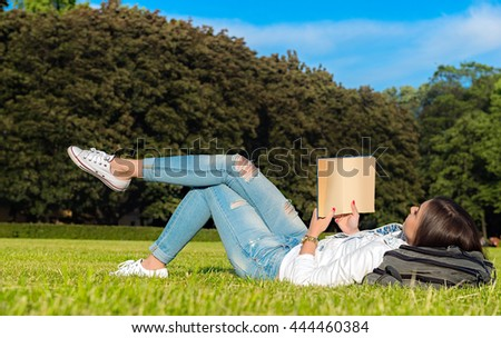 Smiling beautiful young woman on grass and reading book, against background of summer green park. - stock photo