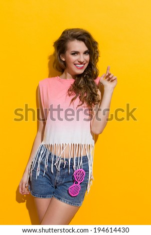 Smiling beautiful young woman pointing up. Three quarter length studio shot on yellow background. - stock photo