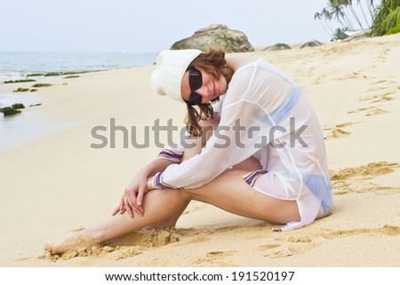 Smiling beautiful young woman portrait  in white hat sitting and sunbathing on the beach sand. Horizontal image