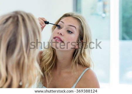Smiling beautiful young woman putting on mascara in the bathroom mirror at home - stock photo