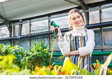 Smiling beautiful young woman standing in orangery and holding garden hose - stock photo
