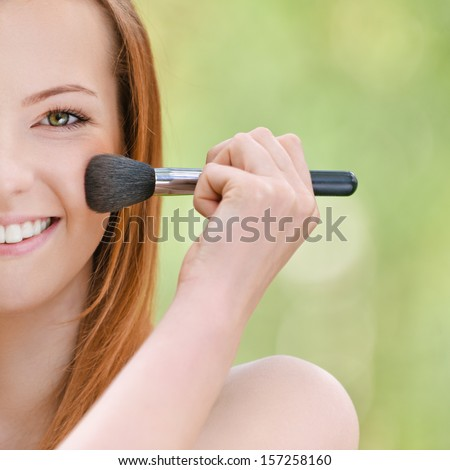 Smiling beautiful young woman with bare shoulders on face powder, against green of summer park. - stock photo