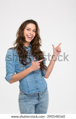 Smiling beautiful young woman with curly hair standing and pointing to the side with both hands over white background - stock photo
