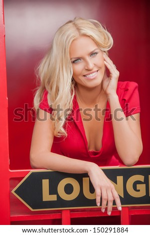 Smiling beauty. Attractive young blond hair woman in red smiling at camera - stock photo