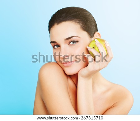 Smiling beauty holding green apple while isolated  - stock photo