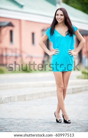 Smiling beauty in blue dress on city streets. - stock photo