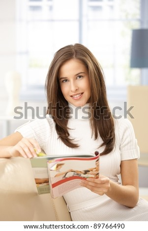 Smiling beauty reading magazine at home, sitting on couch.? - stock photo