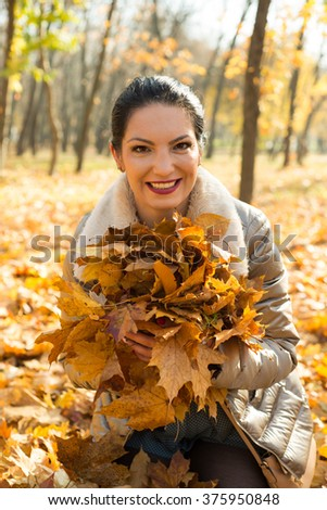 Smiling beauty woman holding plenty autumn leaves