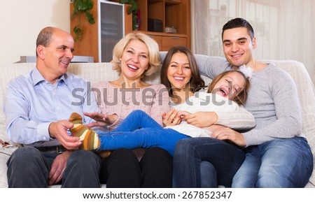 Smiling big united family members together in living room