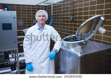Smiling biologist leaning against storage tank in the factory - stock photo