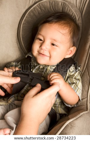 Smiling biracial Asian Filipino kid sitting in car seat while parent hands buckle him up - stock photo