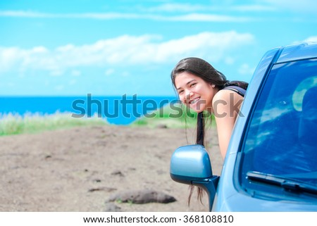 Smiling biracial teen girl leaning out car window on sunny day at  beach with blue Hawaiian ocean in background - stock photo