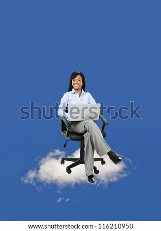 Smiling black businesswoman sitting in office chair on cloud with laptop computer - stock photo