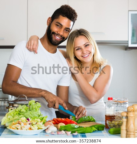 Smiling black guy helping happy white wife preparing healthy dinner  - stock photo