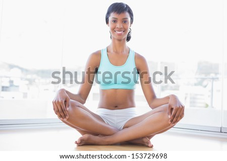 Smiling black haired woman doing yoga in a living room - stock photo